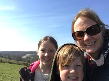 Kate with her two children taking a selfie on top of a hill.