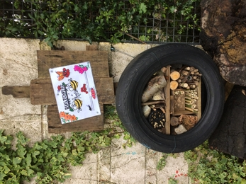 Bug hotel (stacked twigs, logs, etc) inside reused car tire