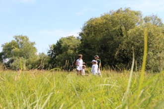 Family in meadow at St Cross Meadow nature reserve