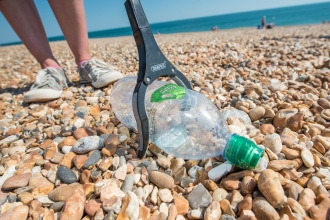 Picking up a plastic bottle on a Hayling Island beach clean organised by Southern Co-op