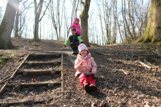 Children sliding down mud slope