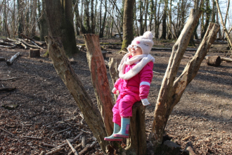 Girl on tree stump, Redlands Year R group at a Forest School session at Swanwick Lakes Nature Reserve