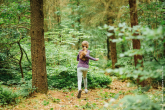 young girl running through woodland