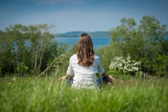 woman in field sat enjoying view