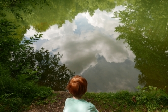 Boy looking into the reflection of Swanwick lakes.
