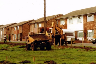 Diggers parked outside residential street preparing to landscape