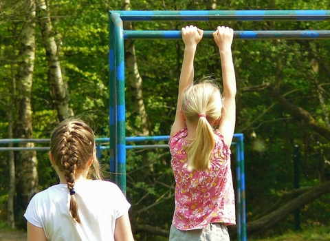 Girl hanging from monkey bars
